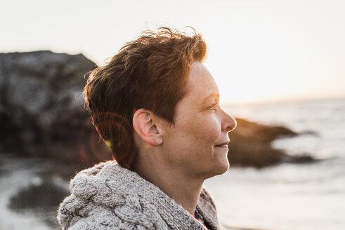 France, Crozon peninsula, portrait of woman on the beach at sunset - UUF008342