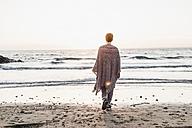 France, Crozon peninsula, woman walking on the beach at sunset - UUF008345