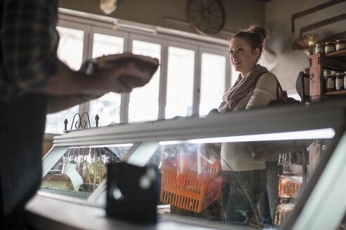 Woman talking to butcher in butchery - ZEF010284