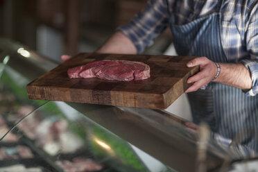 Butcher holding raw steak on wooden board - ZEF010287