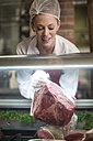 Woman putting meat on display in butchery - ZEF010314