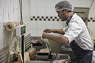 Butcher packing fresh meat in butchery - ZEF010326