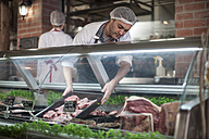 Butcher putting fresh meat on display in butchery - ZEF010338
