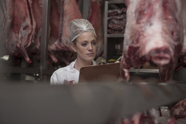 Woman with clipboard in butchery cold store - ZEF010341