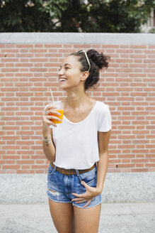 Happy young woman holding orange juice outdoors - MRAF000157