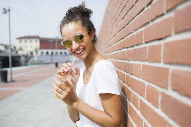 Happy young woman leaning against a brick wall holding orange juice - MRAF000160