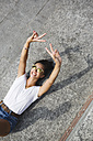 Happy young woman lying down doing V sign - MRAF000163