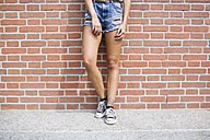 Low section of woman in hot pants leaning against brick wall - MRAF000166