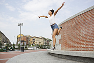 Exuberant young woman jumping outdoors - MRAF000169