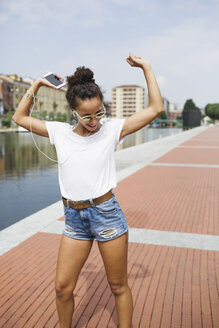 Happy young woman listening to music and dancing at the riverside - MRAF000172