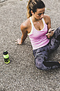Sportive young woman sitting on street with cell phone and drinking bottle - UUF008348