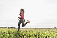Young woman running in rural landscape - UUF008357