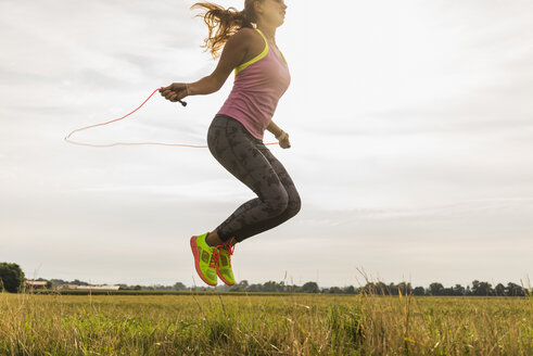 Young woman skipping rope in rural landscape - UUF008360