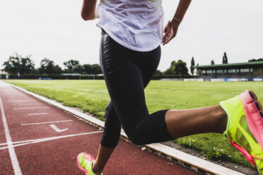 Young woman running on tartan track - UUF008366