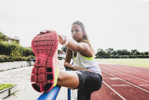 Young woman stretching in a track and field stadium - UUF008369