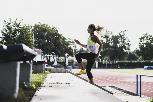 Young woman practicing in a track and field stadium - UUF008372
