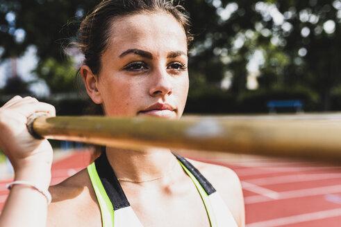 Young woman holding javelin - UUF008378
