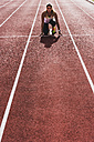 Young woman on tartan track in starting position - UUF008381