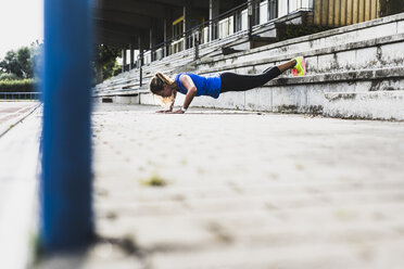 Young woman doing pushups on grandstand - UUF008387