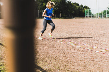Young woman exercising on sports field with agility ladder - UUF008393