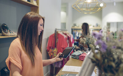 Shop assistant using tablet at counter in a boutique - DAPF000325