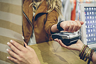 Woman paying using smartwatch with NFC technology in a store - DAPF000328