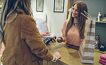 Woman paying using smartphone with NFC technology in a store - DAPF000331