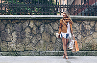 Woman holding shopping bags and takeaway coffee in front of stone wall - DAPF000334