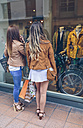 Two women holding shopping bags looking at shop window - DAPF000340