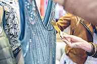 Close-up of woman checking price tag of a dress in a boutique - DAPF000352