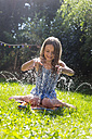 Girl having fun with inflatable water cushion in the garden - SARF002860