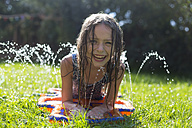 Portrait of laughing girl having fun with inflatable water cushion in the garden - SARF002863