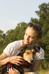 Portrait of young with her dog at sunlight - FCF001071
