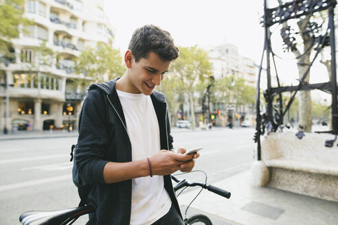 Teenager with a bike in the city, using smartphone - EBSF001729