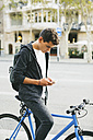 Teenager with a bike in the city, using smartphone - EBSF001732