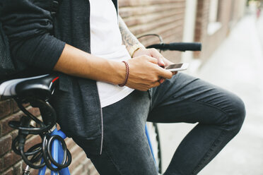 Teenager with a bike in the city, using smartphone - EBSF001747