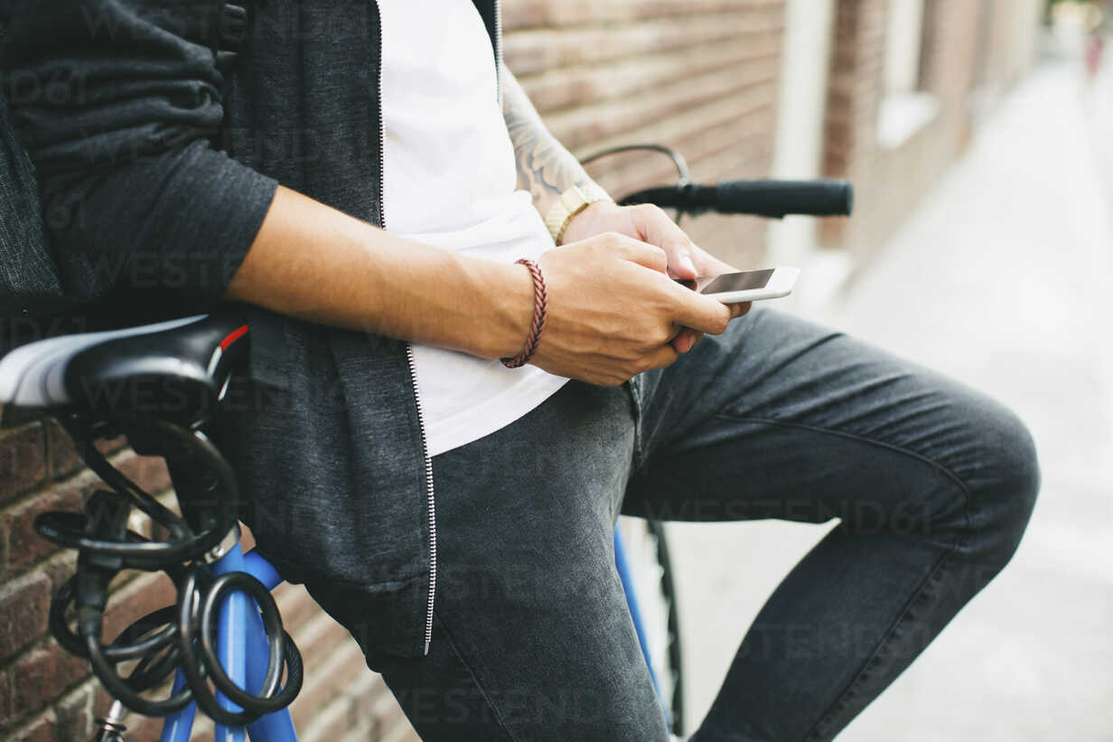 Teenager with a bike in the city, using smartphone - EBSF001747 - Bonninstudio/Westend61