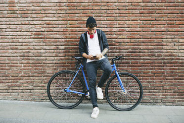 Teenager with a fixie bike, using smartphone - EBSF001750