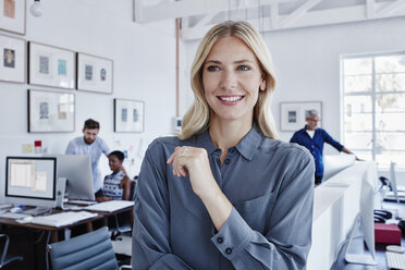 Smiling businesswoman in office with staff in background - RORF00291