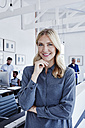 Portrait of smiling businesswoman in office with staff in background - RORF00294