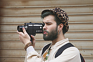 Young man using a vintage video camera - RTBF00341