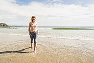 Teenage girl wading in the sea - UUF08400