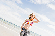 Teenage girl standing on the beach - UUF08403