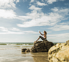 Teenage girl sitting on rock on the beach taking a selfie - UUF08406