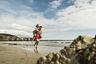 Happy young man carrying girlfriend piggyback on the beach - UUF08409