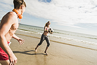 Teenage girl and young man playing with a ball on the beach - UUF08415