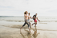 Friends walking with a ball and tyre on the beach - UUF08418