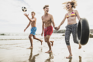 Friends running with a ball and tyre on the beach - UUF08421