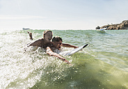 Two friends having fun on surfboard in the sea - UUF08424