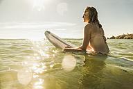 Teenage girl with surfboard in the sea - UUF08436